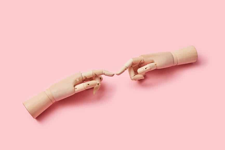 Two Wooden Dummy Fingers Touching.