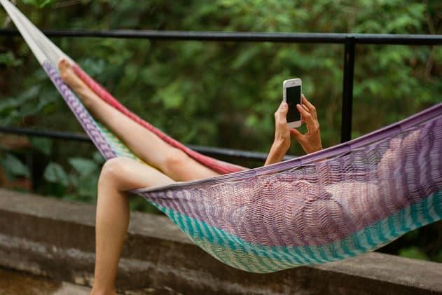Lounging Woman Using Phone In Hammock